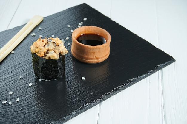Chiuda sulla vista sui sushi di nigiri gunkan sul piatto dell'ardesia isolato su fondo di legno bianco. cibo giapponese per sushi
