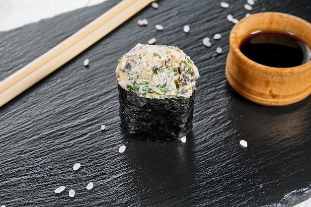 Chiuda sulla vista sui sushi di nigiri sul piatto dell'ardesia isolato su fondo di legno bianco. cibo giapponese per sushi