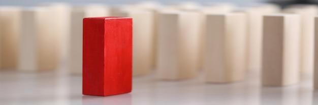 Una vista del primo piano di un blocco di legno rosso con molti mattoni non dipinti
