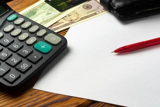 Punta della penna di vista ravvicinata sul foglio di carta con contanti in dollari e calcolatrice sulla scrivania del tavolo.