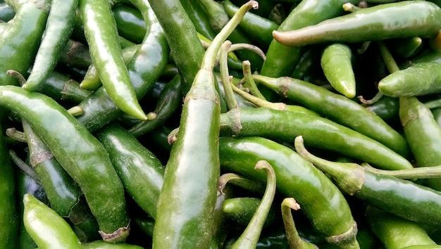 Vista ravvicinata di un mucchio di peperoncino verde nella stagione del raccolto collocato in un mercato o bazar per la vendita