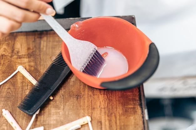 Vista ravvicinata di una spazzola di plastica in una ciotola di tintura per capelli in un parrucchiere