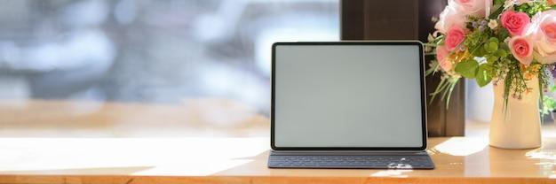 Chiuda sulla vista dell'area di lavoro portatile con la compressa dello schermo in bianco sulla contro barra di legno