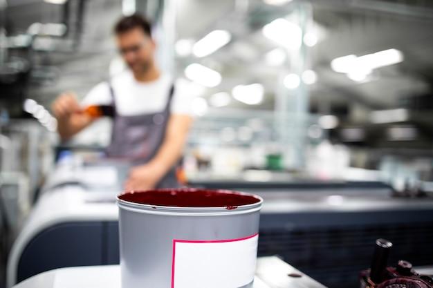 Vista ravvicinata dell'operatore e della macchina da stampa che aggiunge più colore durante il processo di stampa in fabbrica