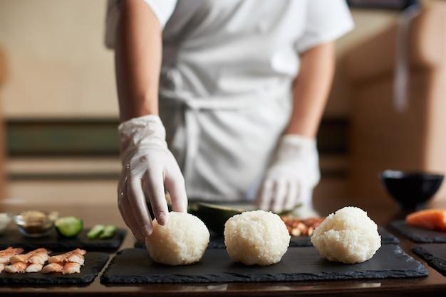 Vista ravvicinata del processo di cottura del sushi di laminazione al ristorante. lo chef sta preparando gli ingredienti per i panini