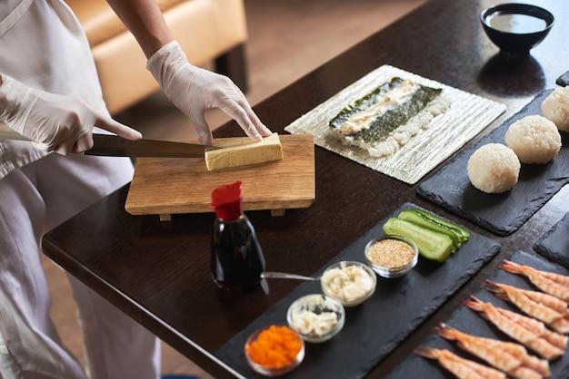 Vista ravvicinata del processo di preparazione del sushi di laminazione. mani in guanti usa e getta per affettare la frittata sulla tavola di legno