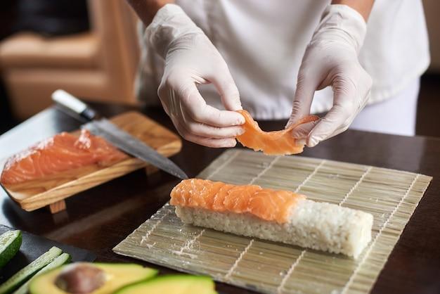 Vista ravvicinata del processo di preparazione del sushi di laminazione con guanti usa e getta sulla stuoia di bambù