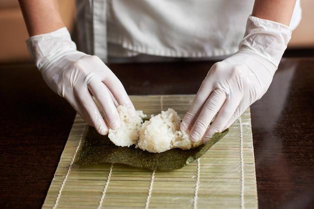 Vista ravvicinata del processo di preparazione del sushi di laminazione