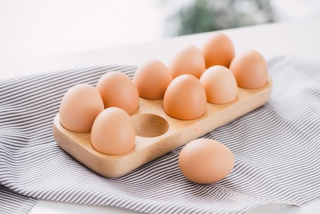 Vista ravvicinata delle uova di gallina crude nella scatola delle uova su sfondo bianco