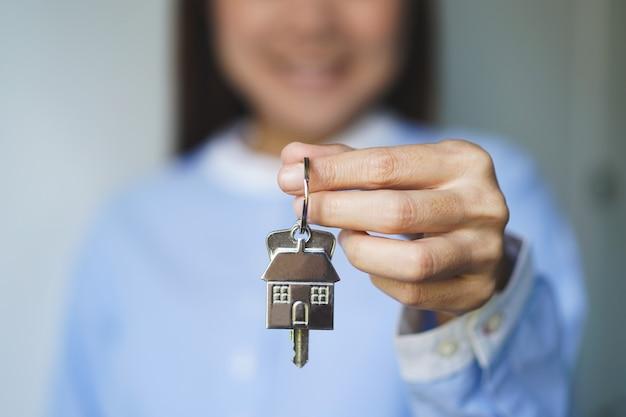 Primo piano vista mediatore agente immobiliare che tiene casa portachiavi