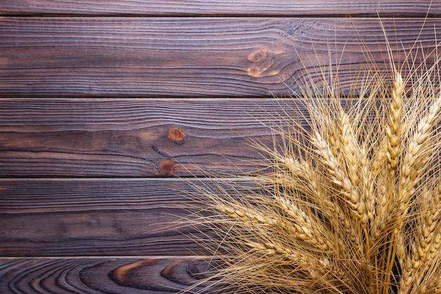 Vista ravvicinata delle spighette di grano maturo sul tavolo di legno rurale