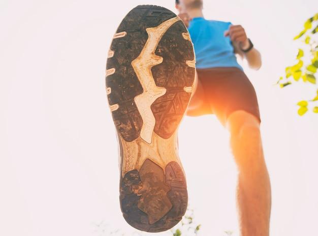 Vista ravvicinata delle scarpe del corridore, che sta correndo attraverso la campagna