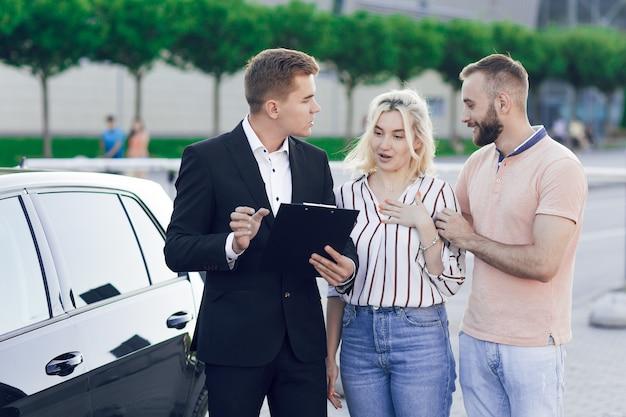 Vista ravvicinata di un venditore e una giovane coppia all'aperto vicino a una nuova auto. il venditore racconta alla giovane coppia della macchina. l'uomo e la donna comprano un'auto.