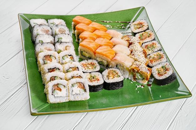 Chiuda sulla vista sull'insieme di rotolo assortito e dei sushi sul piatto verde isolato su fondo di legno bianco. sushi con salmone, anguilla. cibo giapponese per sushi