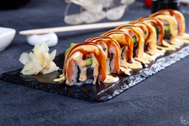 Chiuda sulla vista sull'insieme del rotolo di sushi. california roll con salmone, avocado e caviale servito su pietra nera su oscurità.