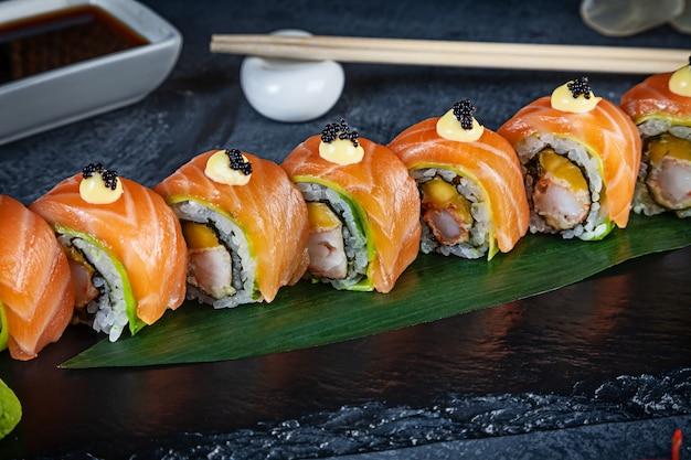 Chiuda sulla vista sul set di rotolo di sushi. rotolare con granchio, avocado, salmone e caviale servito su pietra nera su sfondo scuro. cucina giapponese. copia spazio. sushi servito per menu. cibo sano, frutti di mare