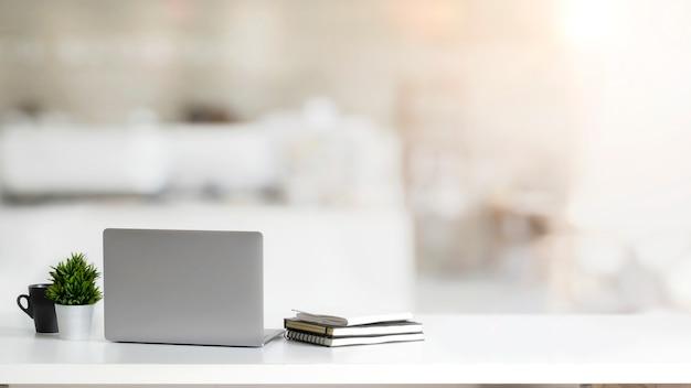 Chiuda sulla vista dell'area di lavoro semplice con il computer portatile, i taccuini, la tazza di caffè e il vaso dell'albero sulla tavola bianca con la stanza vaga dell'ufficio