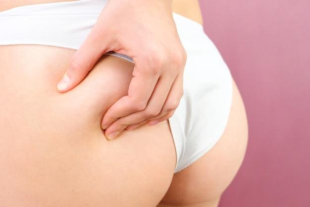 Vista ravvicinata di una donna snella in lingerie su uno sfondo rosa. concetto di problema della cellulite