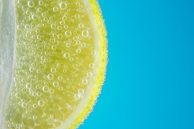 Vista ravvicinata di una fetta di lime in acqua di soda con bolle