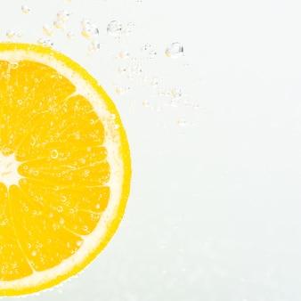 Vista ravvicinata di una fetta d'arancia in acqua di soda con bolle