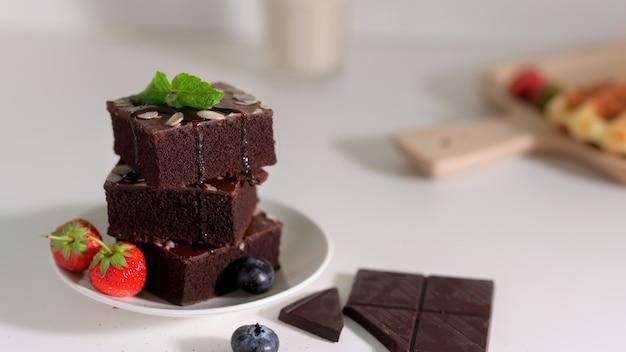 Chiuda sulla vista dei brownie del cioccolato della pila sul piatto bianco con la foglia di menta sulla cima