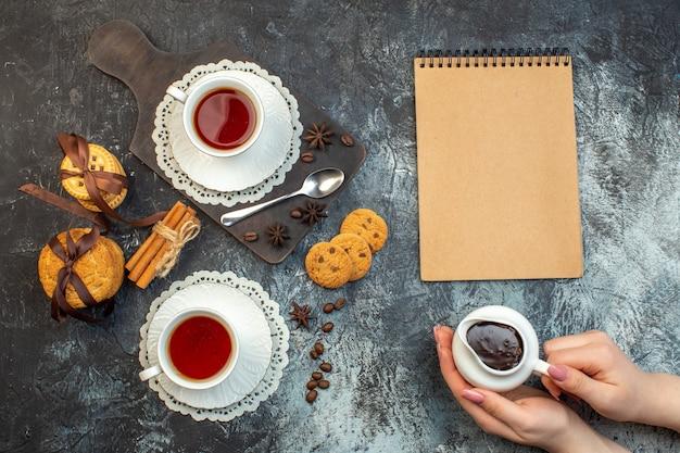 Vista ravvicinata di biscotti impilati lime alla cannella su tagliere di legno e taccuino da tè su sfondo di ghiaccio