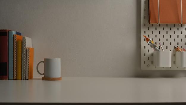 Vista ravvicinata del tavolo di studio con cancelleria libri e copia spazio nella stanza dell'ufficio domestico