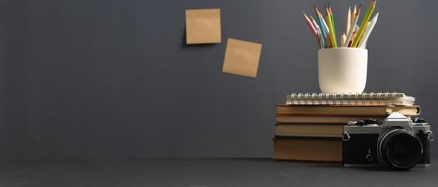 Vista ravvicinata del tavolo di studio con copia spazio, fotocamera, libri e articoli di cancelleria nella stanza dell'home office
