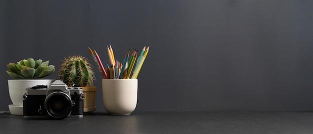 Vista ravvicinata del tavolo di studio con copia spazio, fotocamera, cancelleria e vasi per piante nella stanza dell'ufficio domestico