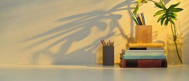Vista ravvicinata del tavolo di studio con copia spazio, cancelleria, libri, elementi e vaso di piante nella stanza dell'home office
