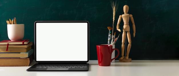 Vista ravvicinata del tavolo di studio con strumenti di pittura libri tavoletta digitale