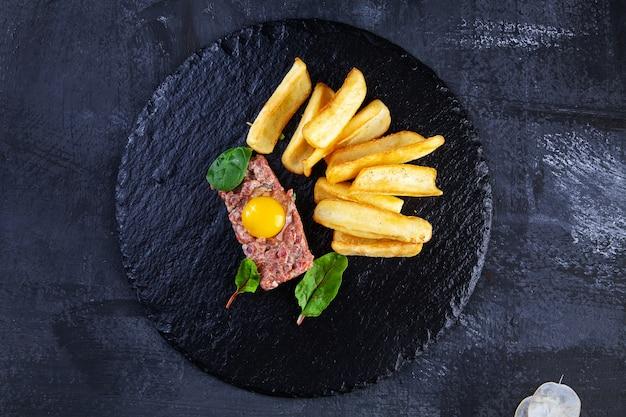 Chiuda sulla vista sulla bistecca alla tartara saporita del manzo servita con tuorlo d'uovo, immersione della patata sul piatto di pietra nero su fondo scuro.