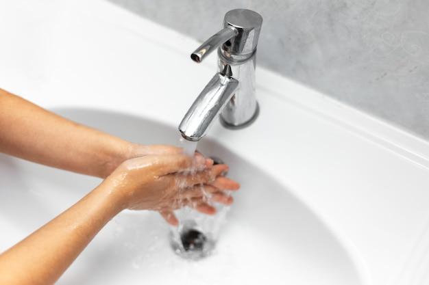 Vista ravvicinata dell'adolescente che si lava le mani sotto il rubinetto dell'acqua nel lavandino bianco