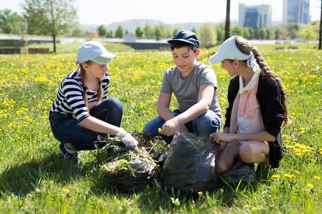 Vista ravvicinata di adolescenti con guanti e sacchi della spazzatura a piedi. concetto di protezione dell'ecologia.