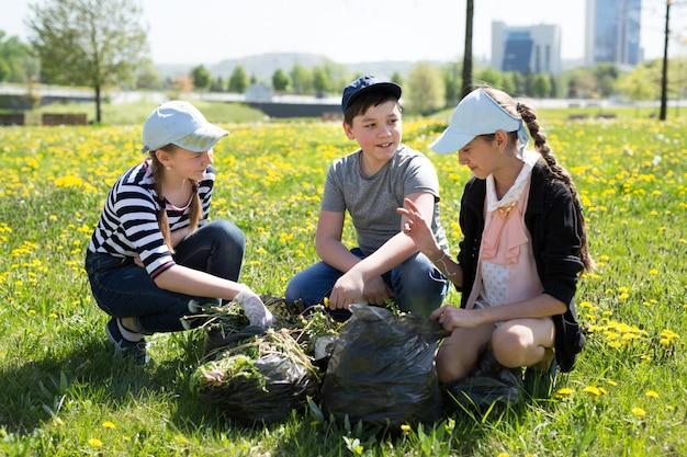 Vista del primo piano degli adolescenti con la camminata dei sacchetti di immondizia e dei guanti. concetto di protezione dell'ecologia.