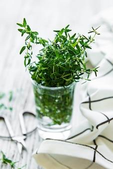 Vista ravvicinata del mazzo di timo. timo verde in un bicchiere