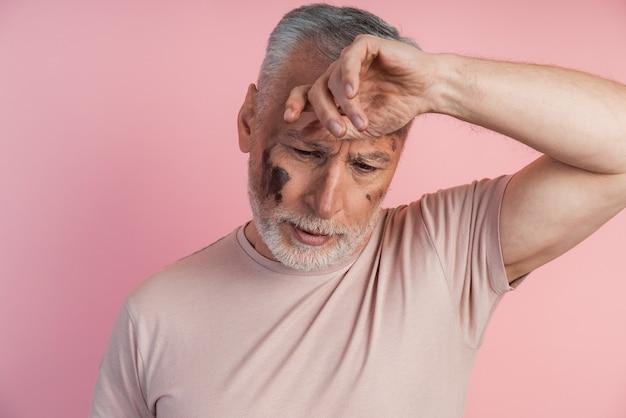 Vista ravvicinata di un uomo stanco su una parete rosa