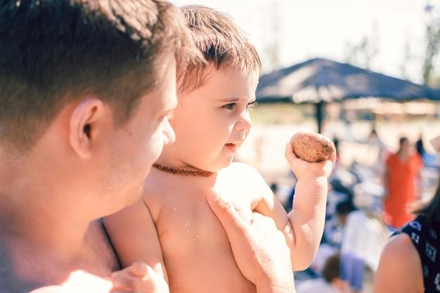 Vista ravvicinata sul bambino e sul padre in una giornata di sole sulla spiaggia.