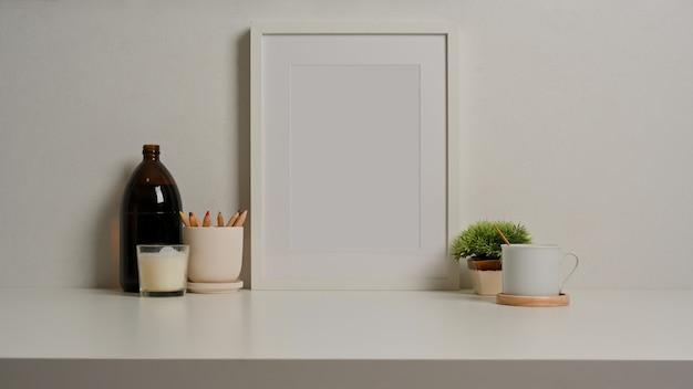 Vista ravvicinata della scrivania bianca con decorazioni della tazza della cancelleria della cornice della foto