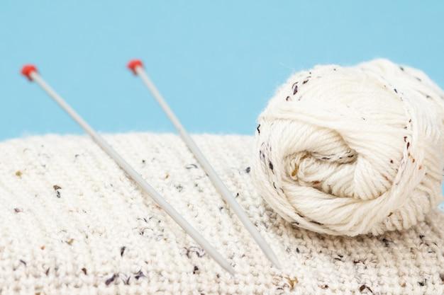 Vista ravvicinata della matassa bianca di filato e pullover con ferri da maglia in metallo su sfondo blu. concetto di maglieria. profondità di campo.