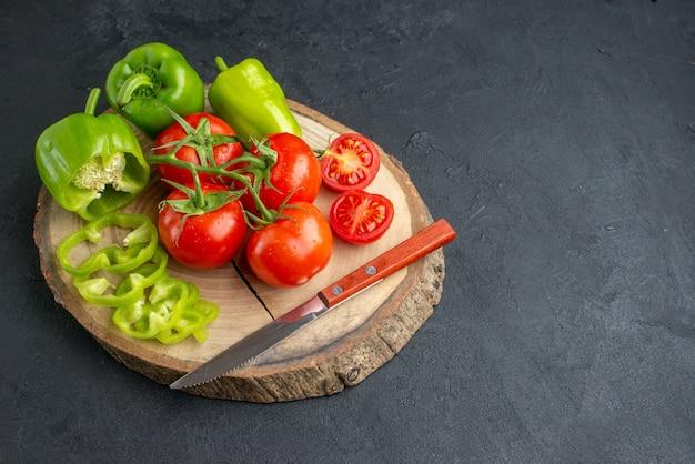 Vista ravvicinata di peperoni verdi tritati tagliati interi e coltello di pomodori freschi su tagliere di legno sul lato destro su superficie nera