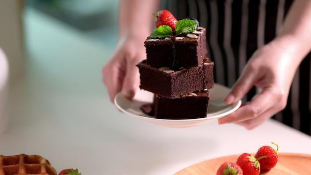 Chiuda sulla vista dei brownie del cioccolato di una pila della tenuta della donna in piatto bianco