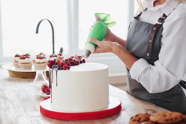Vista ravvicinata della donna che versa la crema sulla torta in cucina.