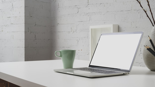 Chiuda sulla vista dell'area di lavoro con il computer portatile dello schermo in bianco, la tazza di caffè e le decorazioni sullo scrittorio con il muro di mattoni
