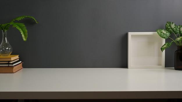 Vista ravvicinata dell'area di lavoro con copia spazio, libri, vasi per piante, mock up frame e copia ritmo in home office