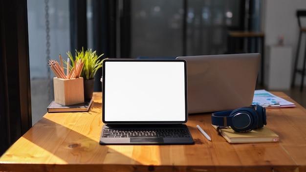 Vista ravvicinata dell'area di lavoro con fotocamera digitale tablet e notebook nel percorso di residuo della potatura meccanica dello spazio di coworking