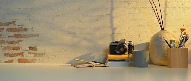 Vista ravvicinata del piano di lavoro con fotocamera, strumenti di pittura, libri, cancelleria e decorazioni