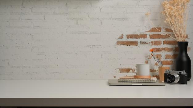 Vista ravvicinata del piano di lavoro con la fotocamera fornisce vaso e copia spazio nella stanza dell'home office