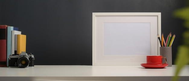 Vista ravvicinata del piano di lavoro con mock up frame, fotocamera, libri, cancelleria e copia spazio in home office