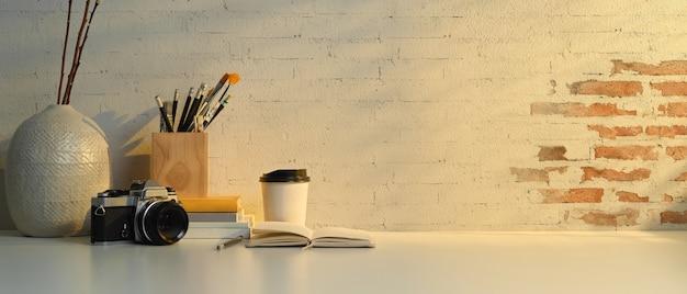 Vista ravvicinata del piano di lavoro con cancelleria, fotocamera, decorazioni e copia spazio in home office